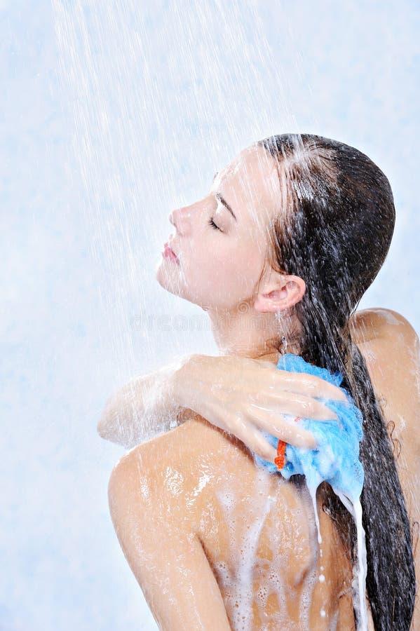 Vrouw die haar lichaam in een douche wast stock foto