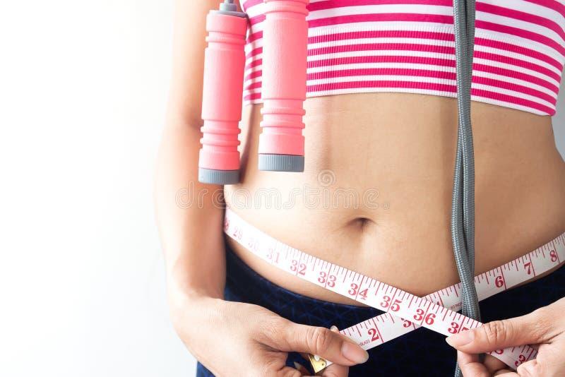 Vrouw die haar lichaam, Gezonde en Dieetlevensstijl meten royalty-vrije stock afbeelding