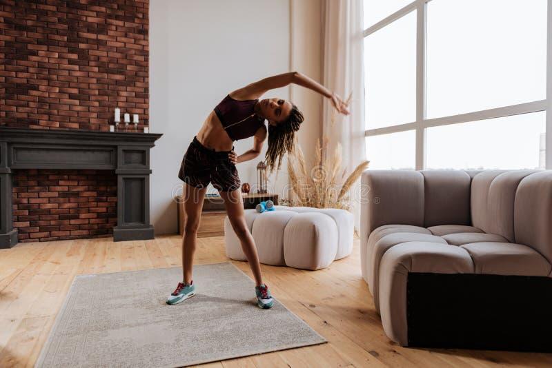 Vrouw die haar lichaam na thuis het beëindigen van training uitrekken stock fotografie