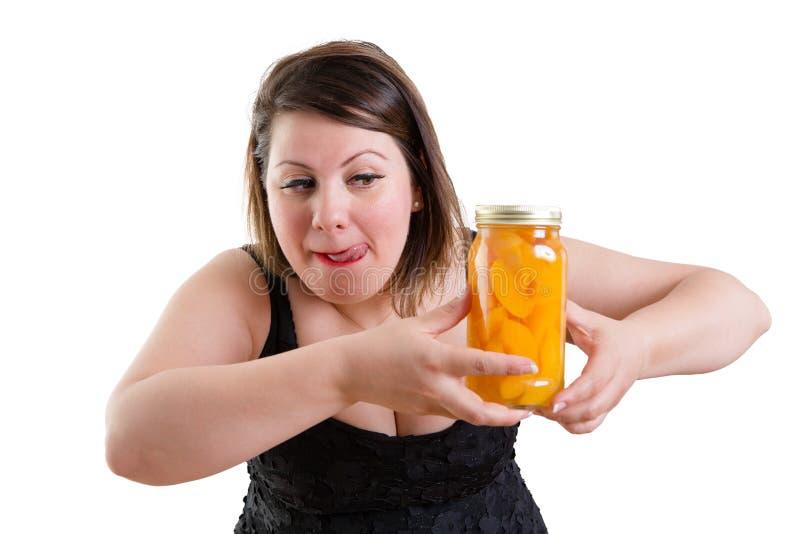 Vrouw die haar lippen likken en een kruik van perziken eyeing stock fotografie