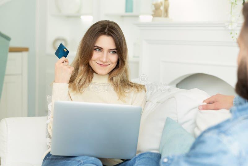 Vrouw die haar man vraagt om haar aankoop online te doen stock afbeeldingen