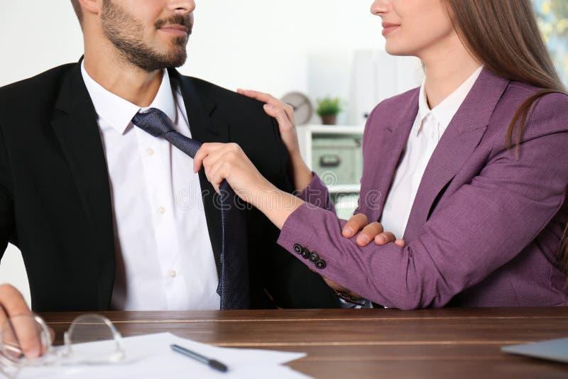 Vrouw die haar mannelijke collega in bureau, close-up lastig vallen stock fotografie
