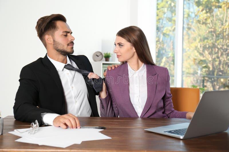 Vrouw die haar mannelijke collega in bureau lastig vallen royalty-vrije stock afbeelding