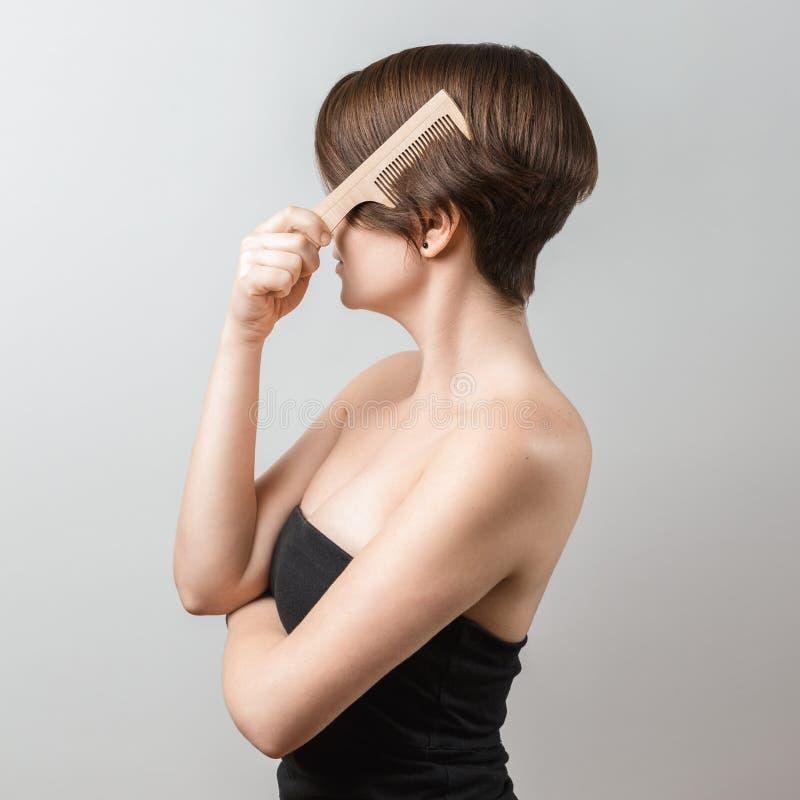Vrouw die haar haar met een houten kam borstelen royalty-vrije stock afbeelding