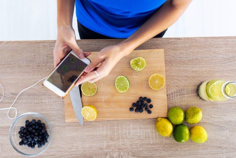 Vrouw die haar mobiele telefoon gebruikt terwijl ze limieten over houten tafel in de keuken snijdt Zenith-weergave royalty-vrije stock afbeeldingen
