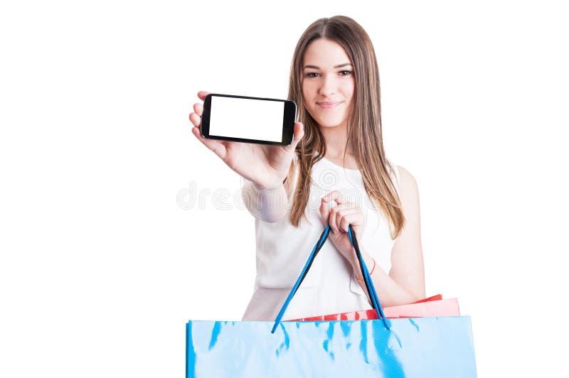 Vrouw die haar mobiele telefoon tonen terwijl het doen van het winkelen royalty-vrije stock afbeelding