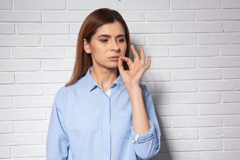 Vrouw die haar mond snellen dichtbij bakstenen muur royalty-vrije stock afbeeldingen