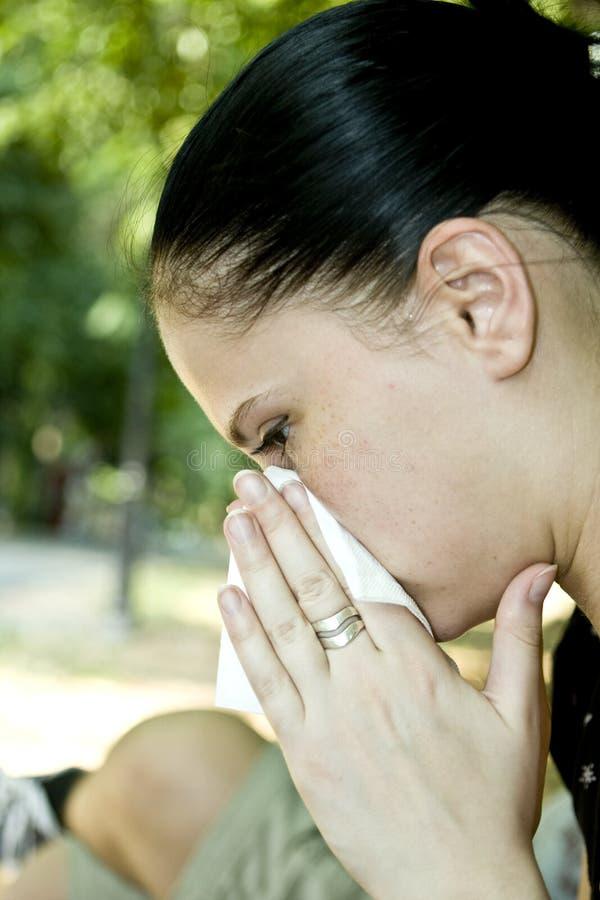 Vrouw die haar neus blaast stock foto's