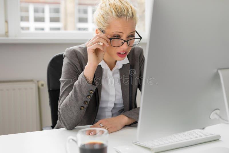 Vrouw die haar ogen drukken om te zien wat op computer is stock foto