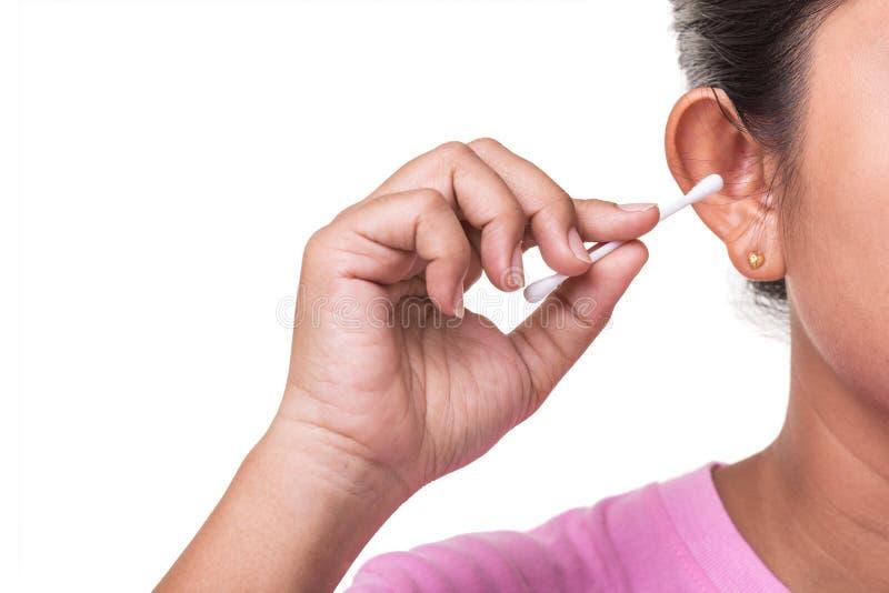 Vrouw die haar oor schoonmaken door katoenen die knopstok te gebruiken op whi wordt geïsoleerd stock afbeeldingen