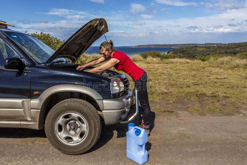 Vrouw die haar opgesplitste auto 4wd bevestigen royalty-vrije stock fotografie