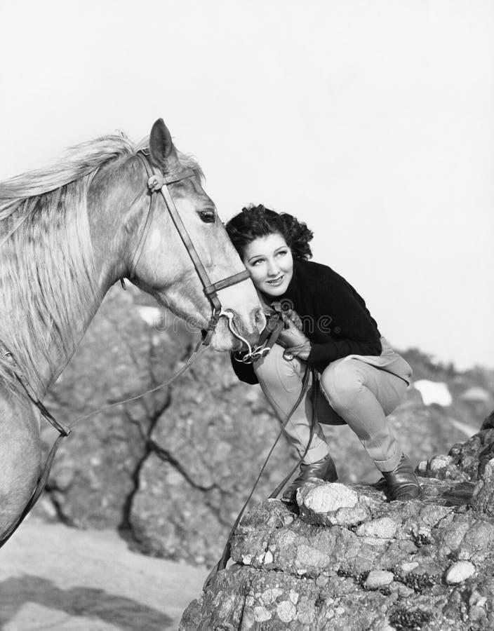 Vrouw die haar paard koesteren (Alle afgeschilderde personen leven niet langer en geen landgoed bestaat Leveranciersgaranties dat royalty-vrije stock foto
