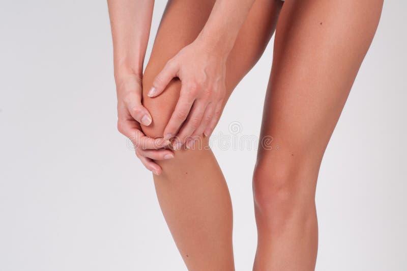Vrouw die haar pijnlijke knie masseren, die pijn in knie voelen stock foto's