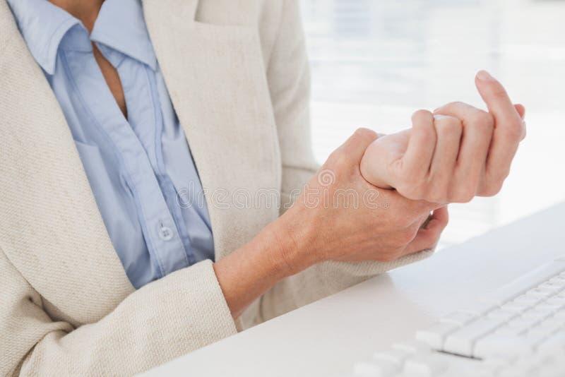 Vrouw die haar pijnlijke pols masseren royalty-vrije stock foto