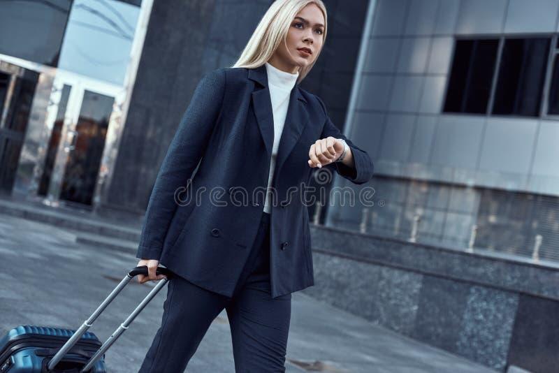 Vrouw die haar polshorloge bekijken terwijl het gaan naar bureau royalty-vrije stock afbeeldingen