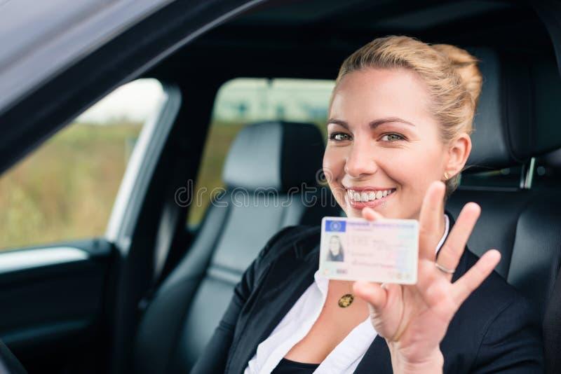 Vrouw die haar rijbewijs tonen uit auto stock foto's