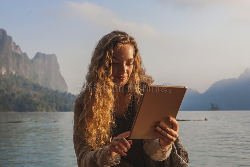 Vrouw die haar tablet gebruiken door een meer royalty-vrije stock foto