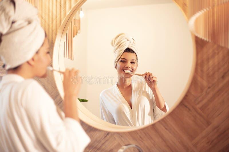 Vrouw die haar tanden in badkamers borstelen royalty-vrije stock afbeeldingen