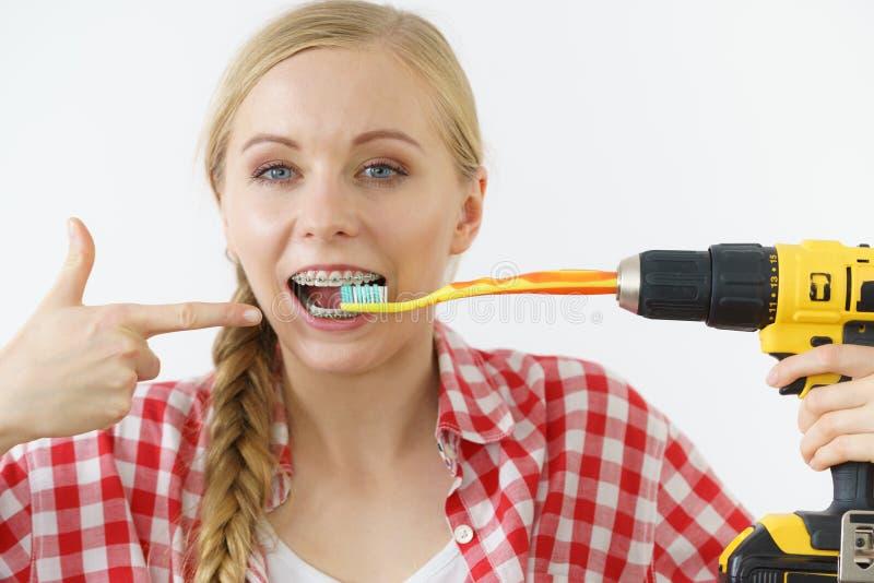 Vrouw die haar tanden burshing die boor gebruiken royalty-vrije stock afbeelding