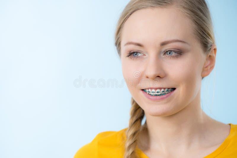 Vrouw die haar tanden met steunen tonen stock foto's