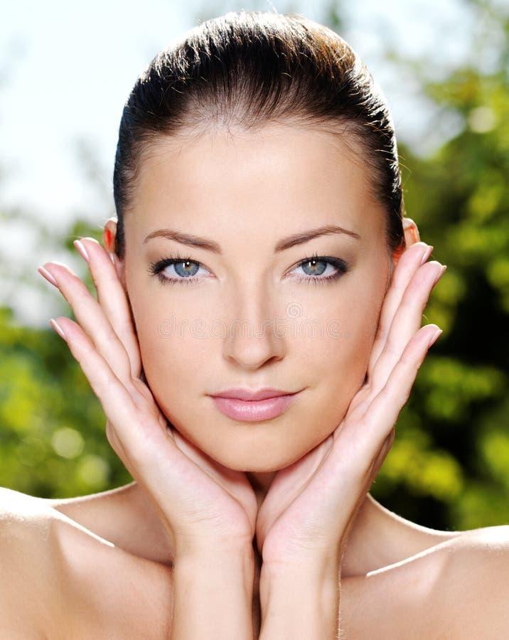 Vrouw die haar verse schone huid van gezicht strijkt stock afbeeldingen