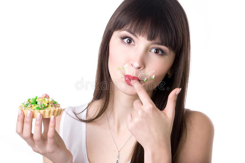 Vrouw die haar vingers likken terwijl het eten van cake stock foto