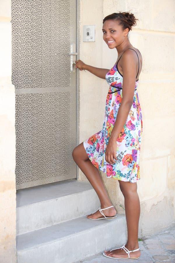 Vrouw die haar voordeur openen royalty-vrije stock foto