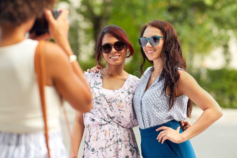 Vrouw die haar vrienden in de zomerpark fotograferen royalty-vrije stock fotografie