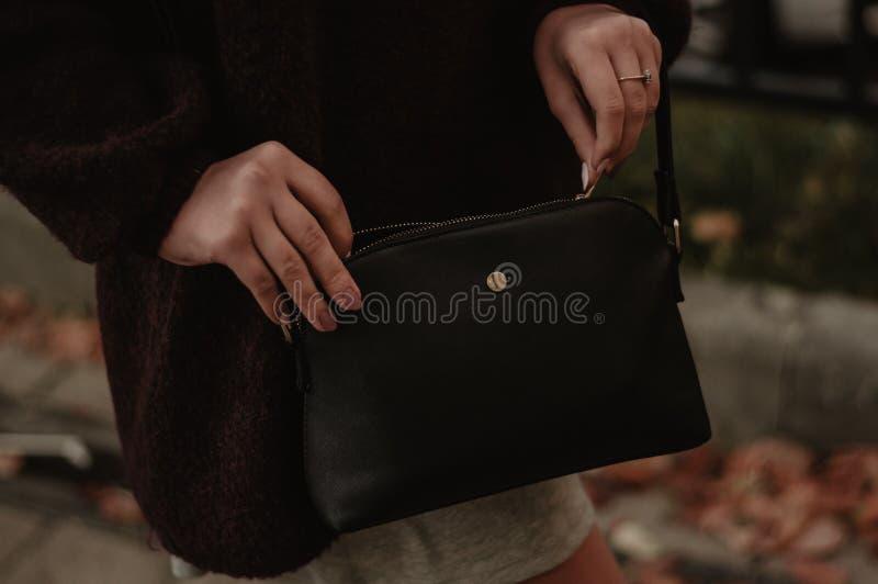 Vrouw die haar zak in openlucht close-up sluiten stock foto