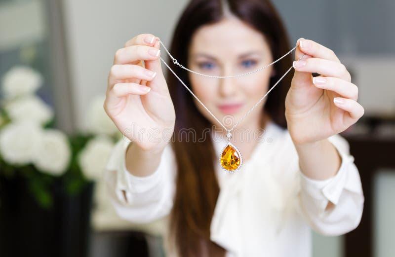 Vrouw die halsband met gele saffier houden royalty-vrije stock fotografie