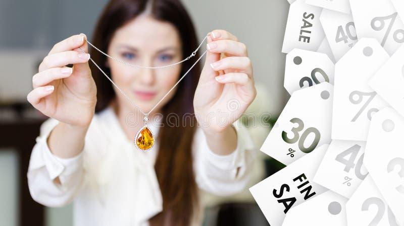 Vrouw die halsband met gele saffier houden Speciale aanbieding royalty-vrije stock foto