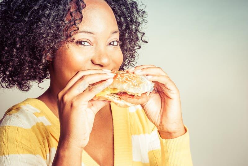 Vrouw die Hamburger eet stock afbeeldingen