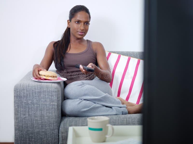 Vrouw die hamburger eet en op TV let stock foto