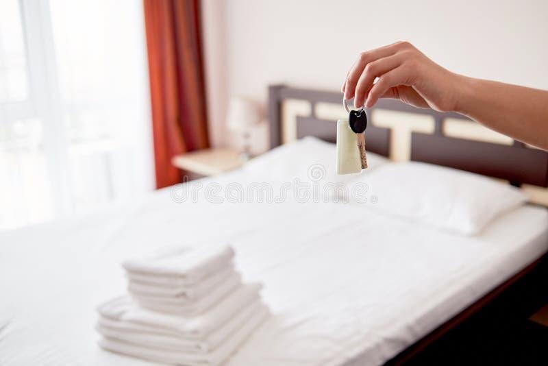 Vrouw die in hand ruimtesleutel met leeg etiket houden bij hotelreeks, exemplaarruimte Slaapkamerbinnenland in onduidelijk beeld stock afbeeldingen