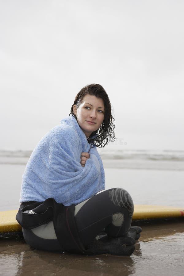 Vrouw die in Handdoek wordt verpakt die weg terwijl het Zitten op Strand eruit zien royalty-vrije stock foto