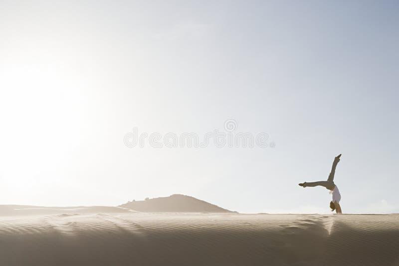Vrouw die handstand in woestijn doen stock afbeeldingen