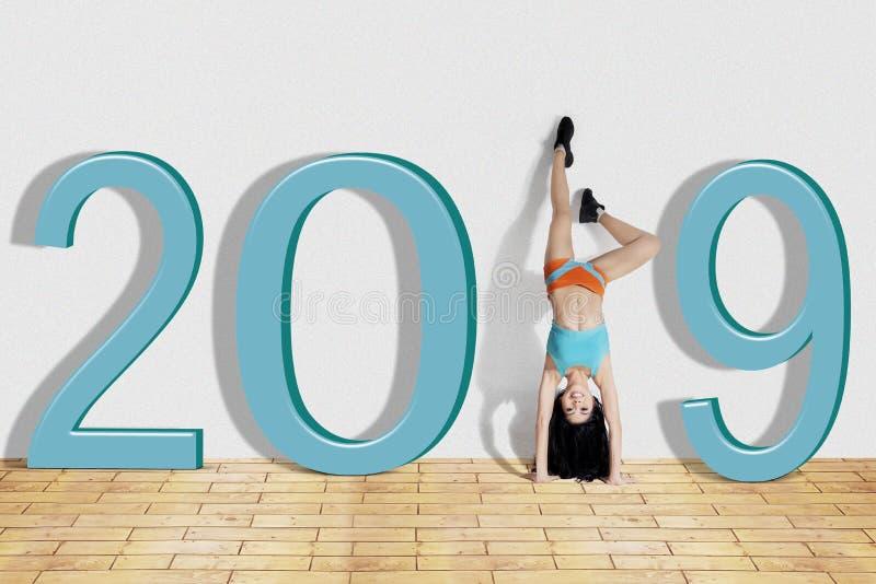 Vrouw die handstandoefening met nummer 2019 doen royalty-vrije stock afbeeldingen