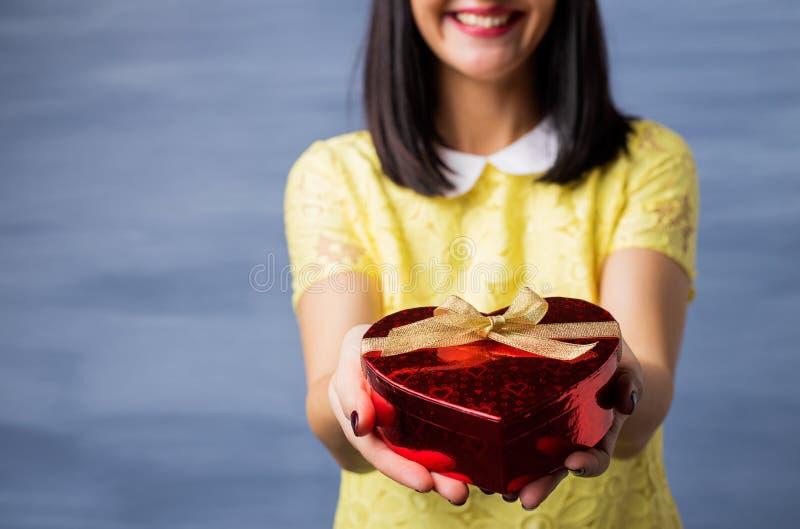 Vrouw die hart gevormde giftdoos voorstellen royalty-vrije stock afbeeldingen