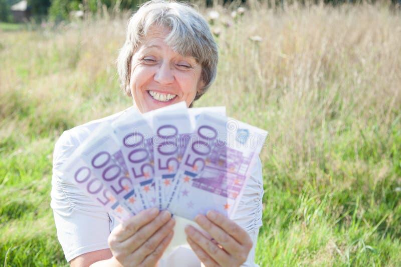 Vrouw die heel wat geld houden stock fotografie