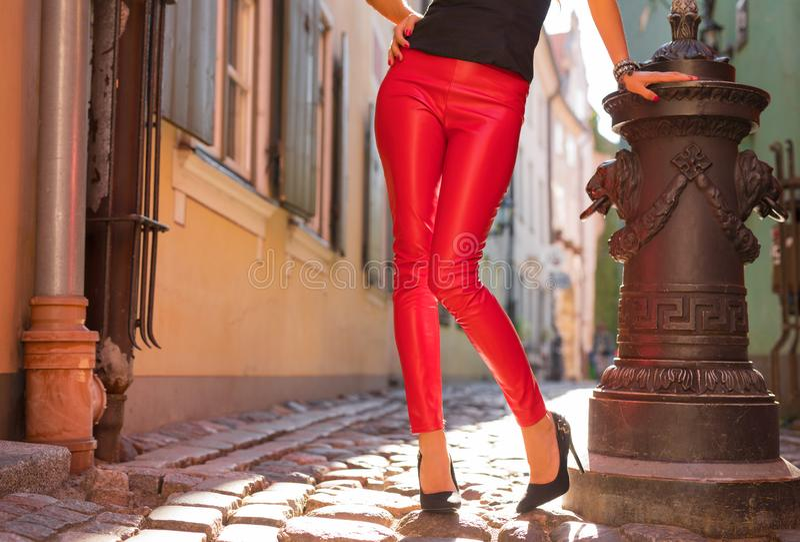 Vrouw die heldere rode leerbroeken en hoge hielen dragen stock foto's
