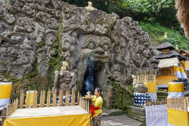 Vrouw die het aanbieden voorbereiden bij de tempel van Goa Gajah, Olifantshol, beroemd Hindoes oriëntatiepunt, Bali, Indonesië, 1 stock fotografie