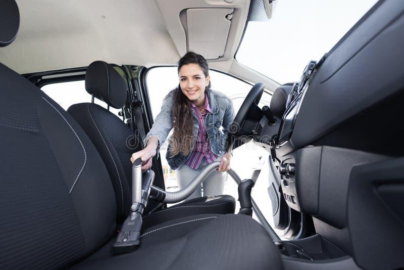 Vrouw die het autobinnenland schoonmaken stock afbeelding