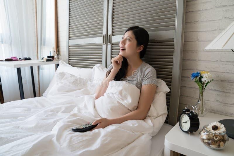 Vrouw die in het bed en wat betreft haar kin liggen royalty-vrije stock afbeelding