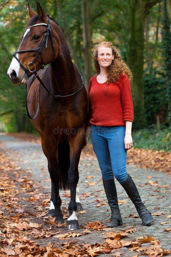 Vrouw die het bruine bos van de de wegsteeg van het merriepaard bevinden zich royalty-vrije stock foto