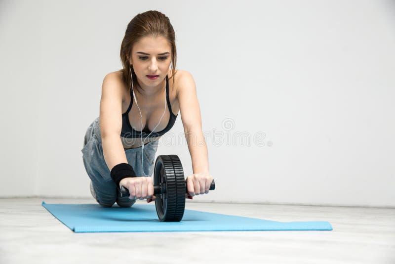 Vrouw die het buikwiel van de geschiktheidstraining uitoefenen stock afbeeldingen