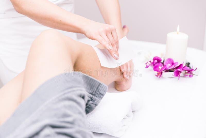 Vrouw die het in de was zetten op haar benen maken royalty-vrije stock afbeelding