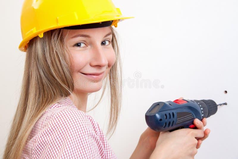 Vrouw die het DIY-werk doen en beschermende helm dragen stock afbeelding