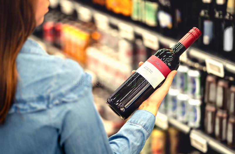 Vrouw die het etiket van rode wijnfles lezen in slijterij of alcoholsectie van supermarkt Plankenhoogtepunt van alcoholische dran royalty-vrije stock fotografie