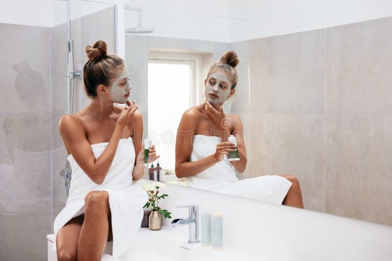 Vrouw die het gezichtsmasker van de modderklei toepassen royalty-vrije stock afbeeldingen