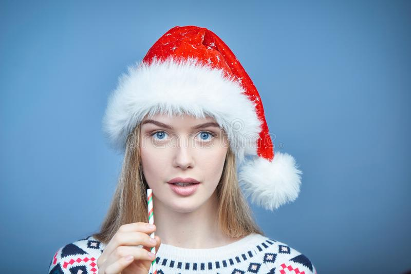 Vrouw die het glas van de holdingsmartini van de Kerstmanhoed met een stro dragen stock foto's